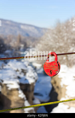 old closed red padlock in heart shape on a background of a winter mountain river canyon close up - Stock Photo