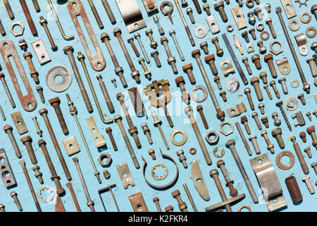 set of old rusty metal screws, nuts and bolts on a blue background. Flat lay, top view - Stock Photo