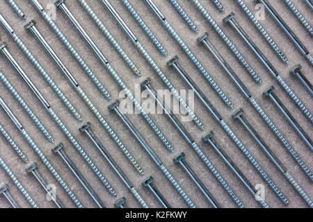set of new metal screws on a grey background are on the diagonal. Flat lay, top view - Stock Photo