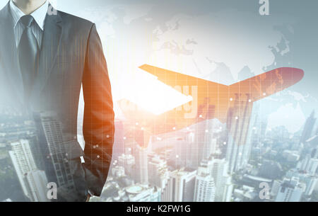 Businessman and airplane with graph, city and world map background - Stock Photo