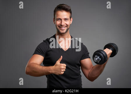 A handsome young man lifting weight smiling and showing thumbs up - Stock Photo