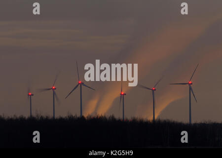 Windmill powered plant in front of the  waste gas plume of the Brown-Coal-fired Power Station at night  . - Stock Photo