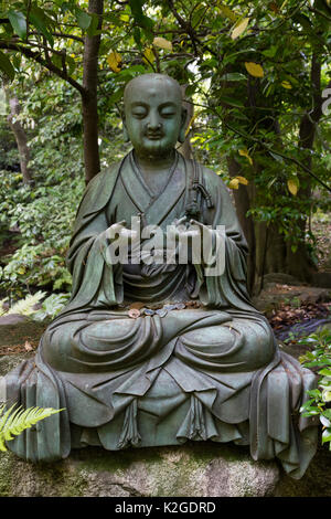 Tokyo, Japan -  Buddha statue with Japanese coins in the garden of the Nezu museum - Stock Photo