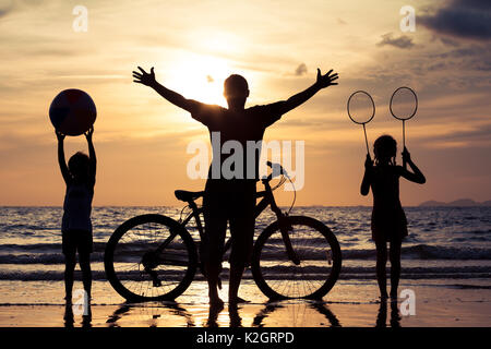 Father and children playing on the beach at the sunset time. Concept of happy friendly family. - Stock Photo