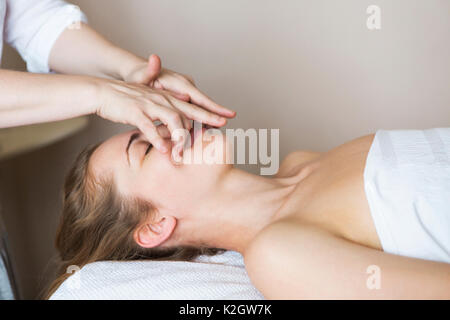 Young pretty woman face massage or beauty treatment in spa salon - Stock Photo