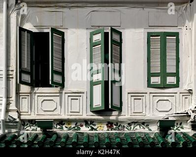 Traditional shop house exterior with green and white wooden louvered shutters, square windows in the Chinatown District - Stock Photo