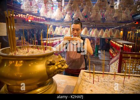 A young man prays at the Man Mo temple, Hong Kong Island - Stock Photo