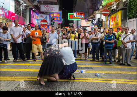 Crowd during live performance in the streets of Mong Kok on a Saturday night. - Stock Photo