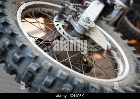 Closeup view of a rear wheel and drive wheel hub of a dirty, grunge motocross motorcycle, which lays on the ground. - Stock Photo