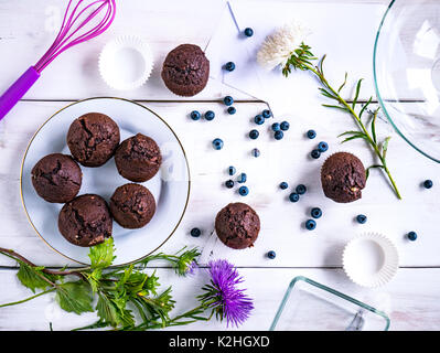 Top view of a white wooden table with muffins and various decorations on it. - Stock Photo