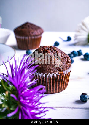 Close-up of chocolate muffins on a white wooden table with various decorations. - Stock Photo