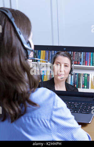 Rear view of a woman in a blue blouse with headset and laptop, making a live video call with the female head of - Stock Photo