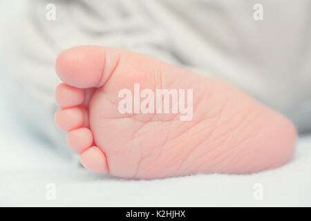 Baby's foot on white blanket in bed - Stock Photo