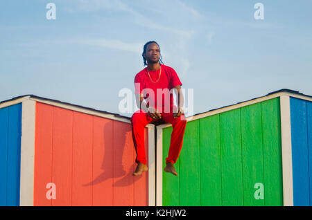 Man sitting on top of colorful beach house - Stock Photo