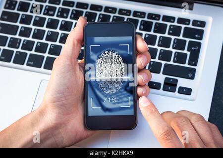Fingerprint scanning on smartphone screen with finger touching biometric digital scanner, identity verification, - Stock Photo