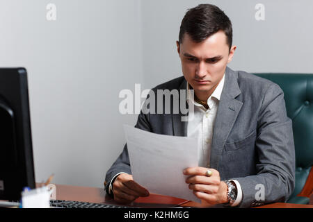 Portrait of business man with paper in hands sitting on chair at table in office - Stock Photo