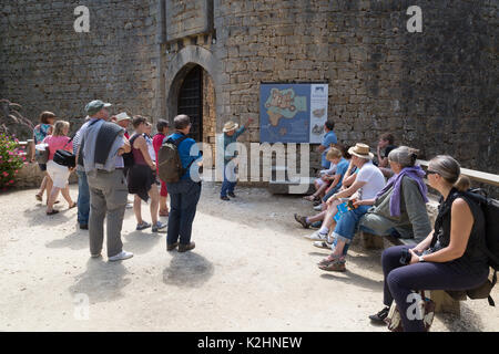 Tourists on a guided tour,  Chateau de Bonaguil, a medieval castle in the Lot valley, Aquitaine France - Stock Photo