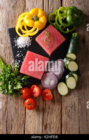 Raw fillet of tuna surrounded by fresh vegetables and spices close-up on a cutting board. Top view from above vertical - Stock Photo