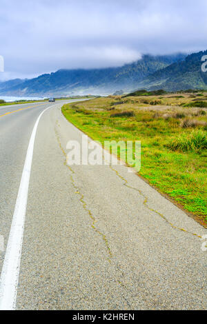Rocky California coast road turns around rugged points of land as it continues north - Stock Photo