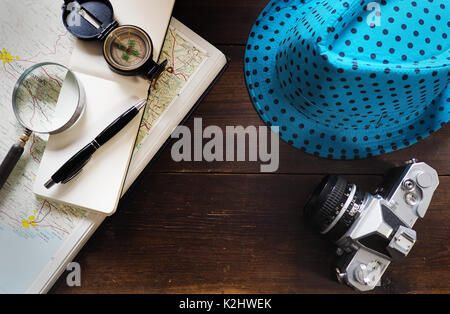 Hat and compass and map on old desk - Stock Photo