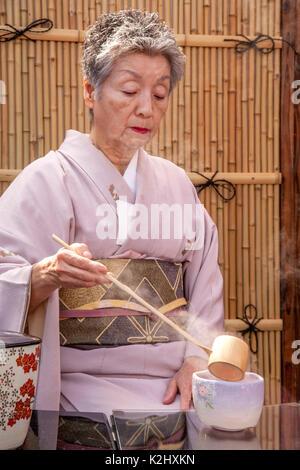 A traditionally dressed Japanese woman in a kimono mixes green tea while demonstrating the Omotesenkei Tea Ceremony - Stock Photo