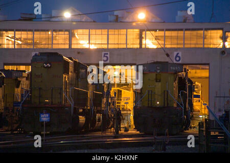 Diesel freight  locomotives are lined up at a railroad yard maintenance shed in Roseville, CA. - Stock Photo