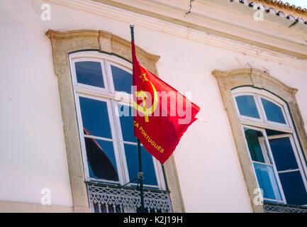 Flag of the Portuguese Communist Party (Partido Comunista Português) on a building in Faro, Portugal. - Stock Photo