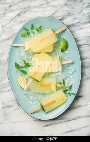 Summer refreshing lemonade popsicles with lime, mint leaves and chipped ice on blue plate over grey marble background, - Stock Photo