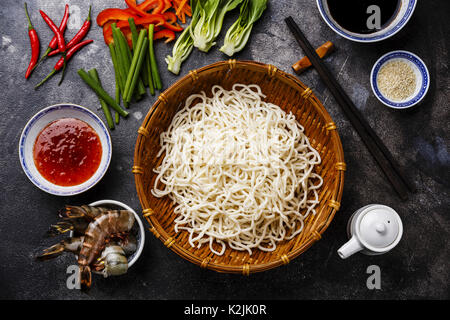 Raw Udon noodles in bamboo basket and Ingredients for cooking asian food with Tiger shrimps, greens, vegetables, - Stock Photo