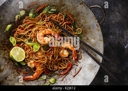 Udon noodles stir-fried with Tiger shrimps and vegetable in wok cooking pan close-up - Stock Photo