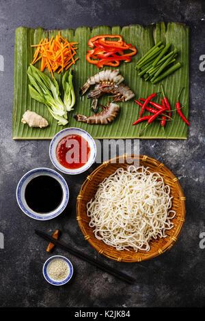 Ingredients for cooking Udon noodles with Tiger shrimps, greens, vegetables, spices on banana leaf on dark background - Stock Photo