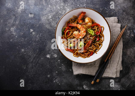 Udon noodles stir-fried with Tiger shrimps and vegetable in bowl on dark background copy space - Stock Photo