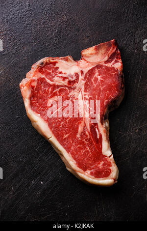 Raw Dry Aged Steak meat T-bone on dark background - Stock Photo