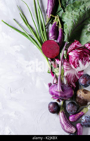 Assortment raw organic of purple vegetables mini eggplants, spring onion, beetroot, radicchio salad, plums, kohlrabi - Stock Photo