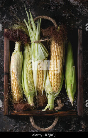 Young raw uncooked corn cobs in leaves in wooden tray. Top view over dark brown concrete texture background. - Stock Photo