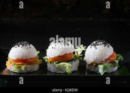 Mini rice sushi burgers with smoked salmon, green salad and sauces, black sesame served on black square plate with - Stock Photo
