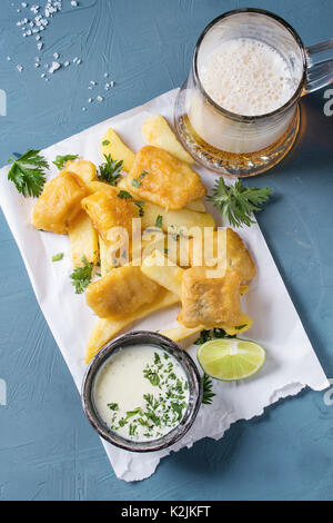 Traditional british fast food fish and chips. Served with white cheese sauce, lime, parsley, glass of lager beer - Stock Photo