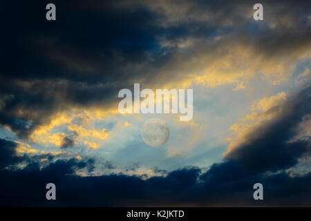 After a violent thunderstorm, between dark clouds still full of rain, backlit by sunset, there is the full moon - Stock Photo