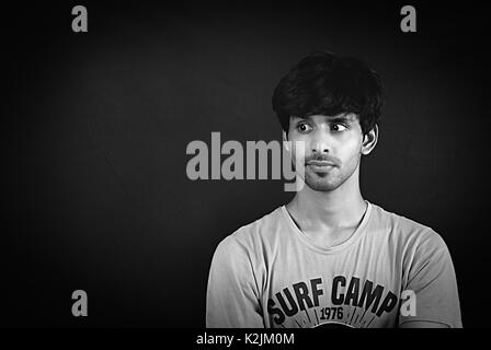 monochrome picture of a smart Asian young boy looking confused in a studio concept shoot with black background - Stock Photo