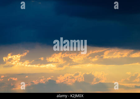 After a violent thunderstorm, at the top dark rain clouds, below a warm sunset - Stock Photo