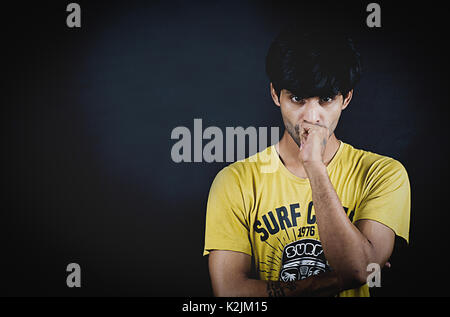 Smart Asian young boy looking tensed in a studio concept shoot with black background - Stock Photo