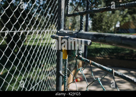 old rusty chain fence gate with lock open - Stock Photo