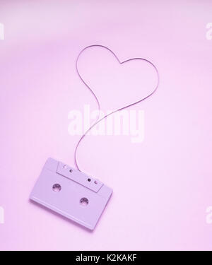 Creative love concept photo of painted cassette with tape in the shape of heart on pink  background. - Stock Photo