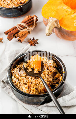 Dietary autumn pastries, breakfast. Crumble pumpkin pie, maple syrup and oatmeal flakes, in plate saucers, on a - Stock Photo