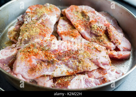 Uncooked pork steaks with seasoning - Stock Photo