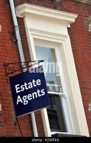 an estate agency sign hanging outside of a Victorian or Edwardian building next to a window on a cast iron frame - Stock Photo