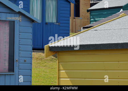 Brightly coloured beach huts on the seashore in a coastal scene on the beach Isle of Wight holida homes and chalets - Stock Photo