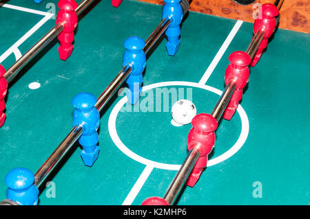 Red and blue teams lined up for the kick-off in a game of table football - Stock Photo