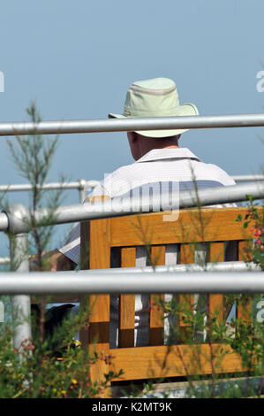 an elderly gentleman looking out to sea sitting on a bench deep in thought older man retired and thinking - Stock Photo