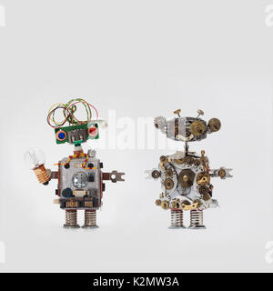 Futuristic robots on gray background. Friendly mechanical toys with electrical wire hairstyle, colored blue red - Stock Photo